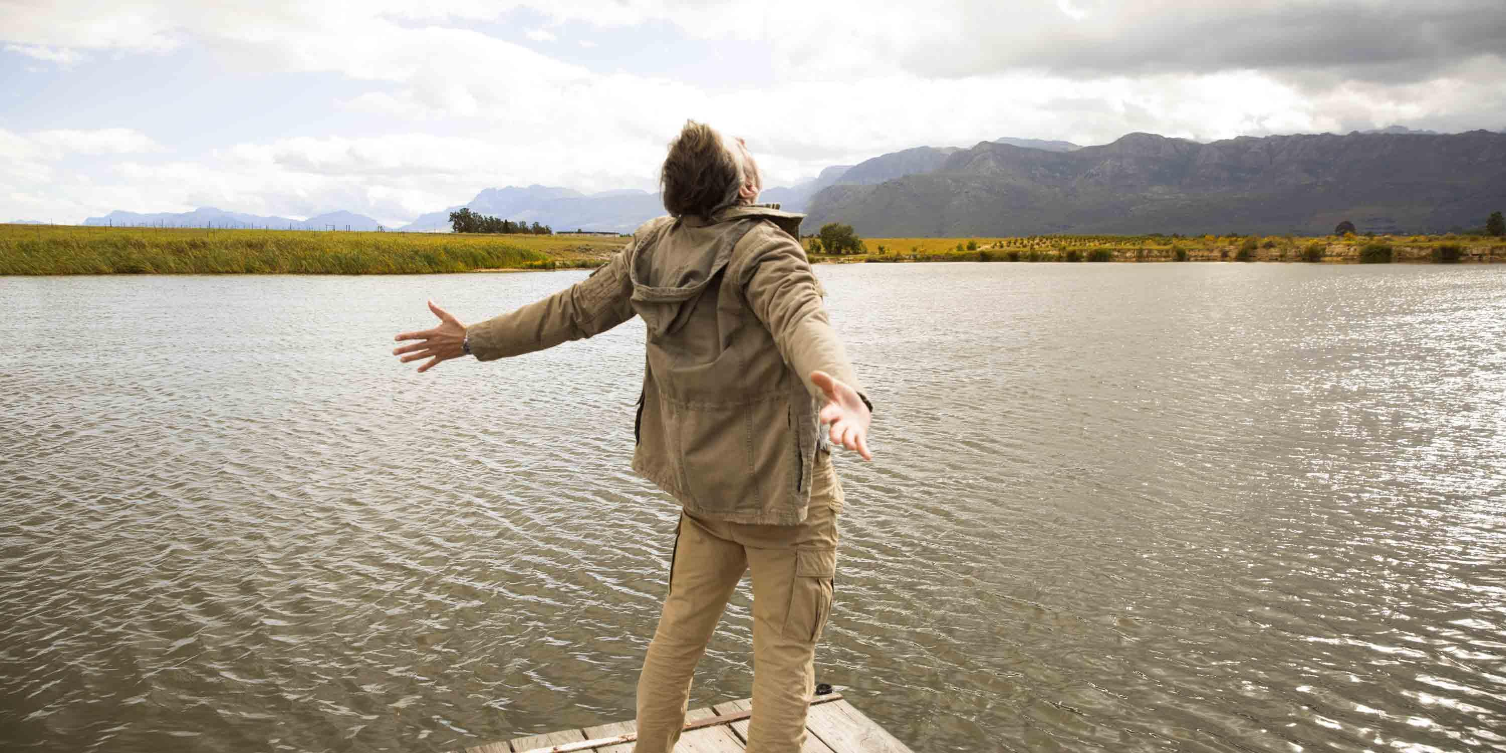 man-senior-standing-at-lake-open-arms