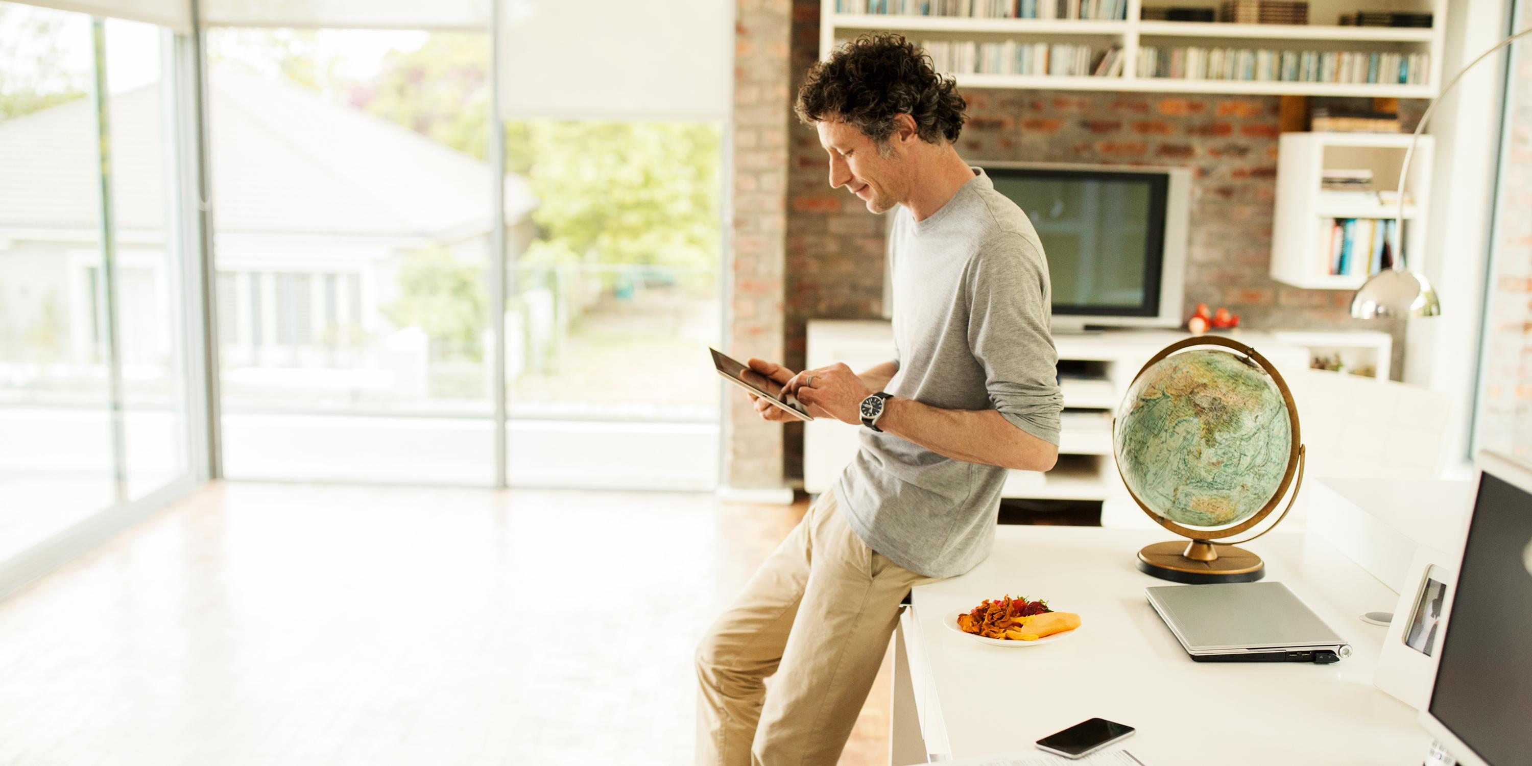 man looking at tablet living room