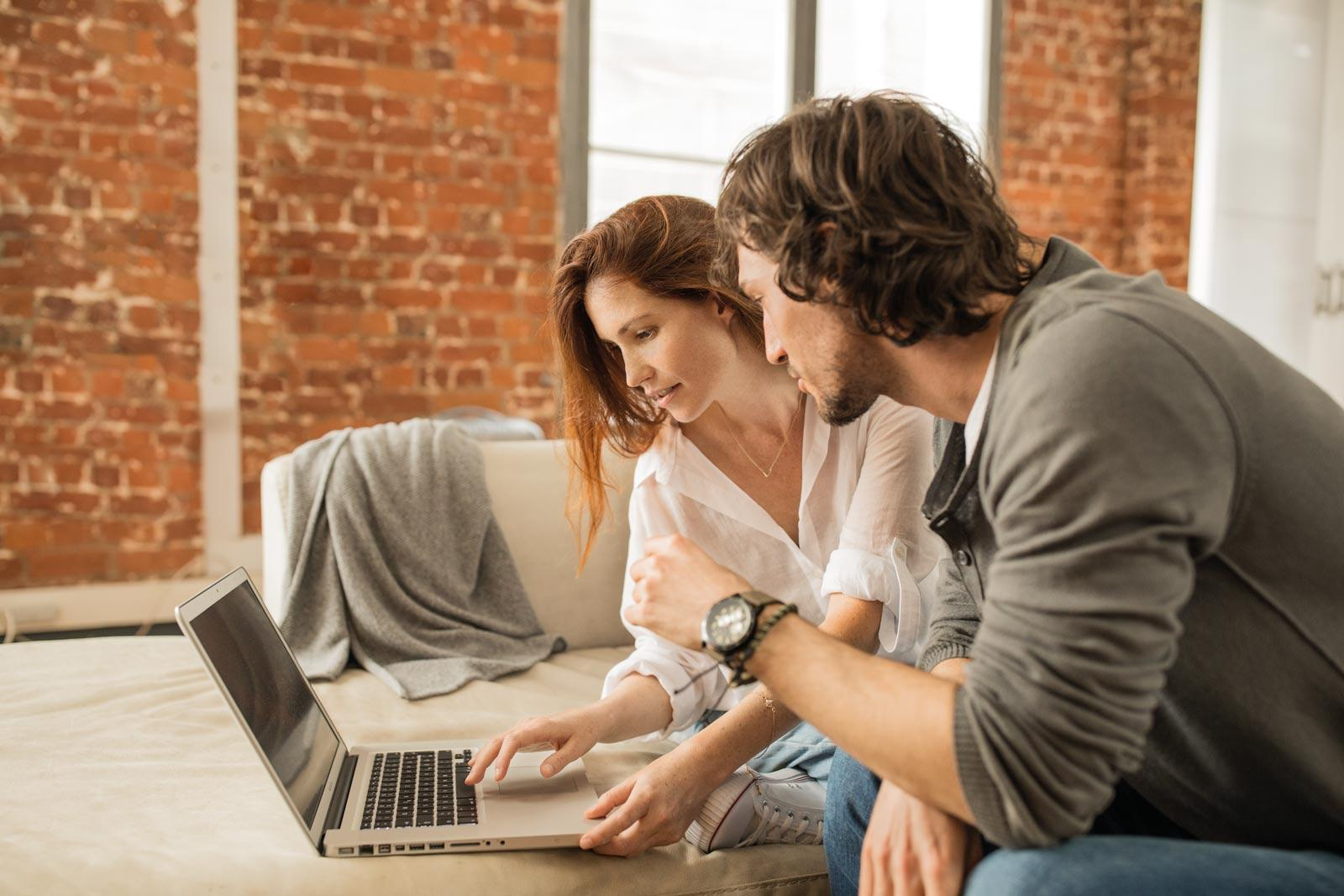 young-couple-sitting-in-front-of-laptop
