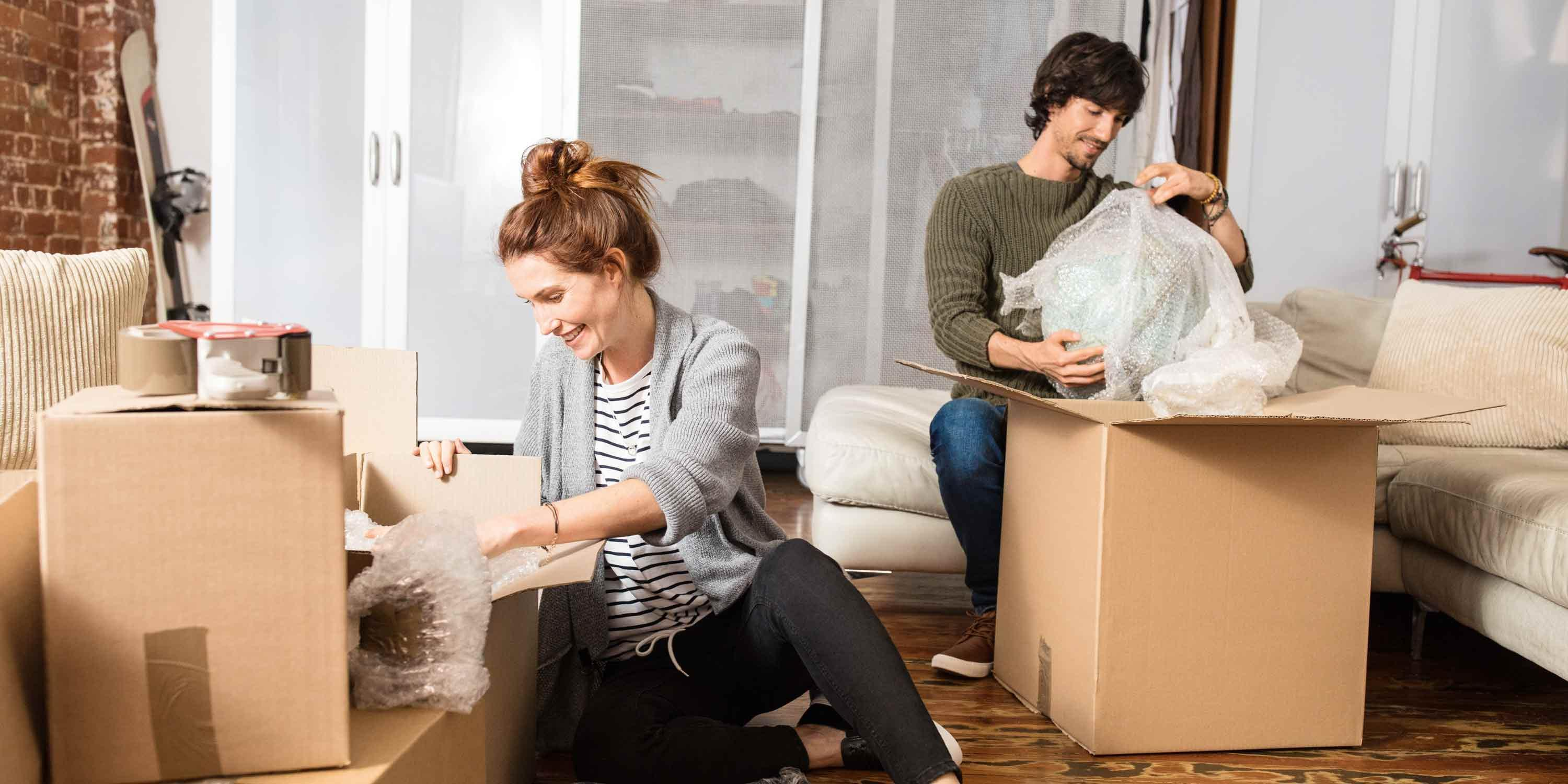 young-couple-unpacks-cartons-moving-boxes